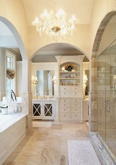 master bathroom MY DREAM... everything from the white cabinetry, creamy walls, stone floor and shower, stunning chandelier, and ahh-mazing soaking tub
