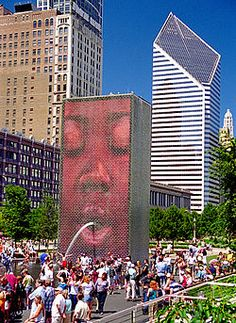 image of 50-foot-tall (15 m) architectural structure spouting water on children from a hole in its face. There is an image of a human face positioned such that the water appears to spout from the mouth. Blue sky and tall buildings are in the background.