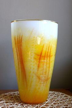 Looking for a vase to showcase spring flowers in all their glory? This handblown glass vase would make a lovely addition your Easter table. Luscious buttery yellow with harvest gold accents looks great with flowers or as a standalone piece on your mantel, kitchen table, bedside or wherever a sharp accent of colour is wanted.   Measures approximately 13 inches tall (33 cm), 4.3 inches (11 cm) in diameter at the base, and 7.5 inches (19 cm) in diameter at the top.