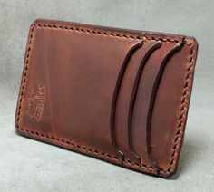 Hand cut and stitched leather minimalist wallet. A minimalist wallet made with quality vegetable tanned leather that features 3 pockets for I.D. and cards etc.. a unique cash strap/card holder on t...