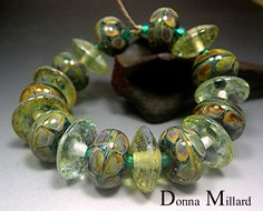 Loaded with lots of silver. Each bead has been wrapped in pure silver leaf. 9 of the beads have been decorated with a lovely color shifting glass with many colors ranging from browns, golds, greens, teals, blue and purple.