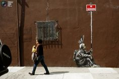 A woman walks past a drawing, believed to be the work of elusive British street artist Banksy, in the Mission District of San Francisco, Calfornia.