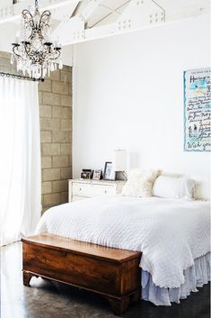 White bedroom with exposed brick wall and crystal chandelier