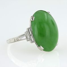 A bright and beautiful vibrant green translucent oval jade cabochon is elegantly presented in a finely crafted platinum mounting with a geometric array of baguette-cut diamonds on either side and a small acanthus leaf engraved detail on the top of the ring shank. A sleek and original Art Deco ring, circa 1930s.