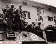 The armored force reaches downtown Berchtesgaden. These 3rd Infantry Division GIs riding on an M36 tank destroyer are viewing the Berchtesgaden World War I memorial, painted above the arcades in the palace square.