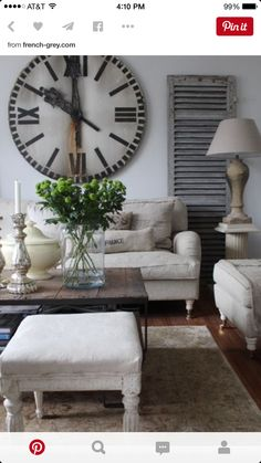 shutter door as wall art huge clock classic bone colored furniture with rustic wood coffee table pop of greenery nice living room