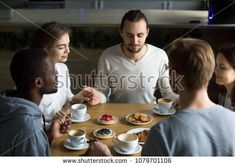 Grateful multiracial young friends holding hands sitting at home or cafeteria table saying grace concept, religious people blessing food praying meditating thanks before eating breakfast together Friends Holding Hands, Saying Grace, Cafeteria Table, Man Praying, Grateful, Thankful, Religious People, Eat Breakfast, Blessing