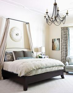 Gracious Family Home - Wheat-colored bed curtains add height and drama to the master bedroom. The coffee-and-cream color palette is accented by a painting by Christina Marie Long.