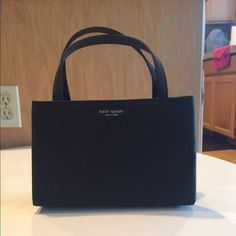 Kate spade purse. Very cute Kate spade purse. Purse measures 5 1/4in tall x 8in long and 2 3/4in wide.   Rigid purse with 1 small zippered pocket inside. In mint condition! kate spade Bags Mini Bags