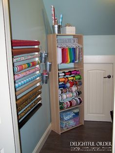 could do this with my old ikea bookshelf... Gift wrap organization - two pieces of painted wood with cafe curtain rods to hold gift wrap rolls and ribbon spools; buckets for scissors and other supplies; tissue paper on hangers; gift storage at bottom of cabinet; box at top of cabinet for greeting cards.