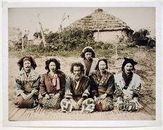Ainu, Japan. ca. 1890 / Five Ainu women and one Ainu man sit outside a straw hut in an outdoor setting. Many Ainu women tattooed their lips in mustache-shaped patterns to indicate their eligibility for marriage. Photographer unidentified.