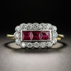 Sweet, petite and precious, this delightful Edwardian style jewel, rendered in two-tone 18K gold, radiates in the center with a trio of rich red scissor-cut rubies bordered all around with small sparkling white round brilliant-cut diamonds, 9/16 by 5/16 inch, currently ring size 7 1/4.