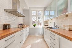 cuisine blanche en deux lignes équipée de deux plans de travail en bois massif et crédence en carrelage métro blanc