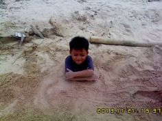 my kid inside of the sand