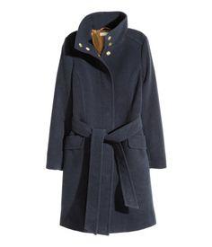 Dunkelblau. Leicht ausgestellter Mantel aus gefilzter Qualität. Modell mit Stehkragen und verdeckten Druckknöpfen vorn. Bindegürtel in der Taille und