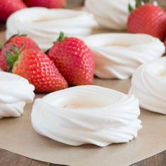 Piped meringue nests surrounded by fresh strawberries.