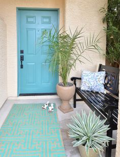 Update a porch quickly with a painted front door, black bench, rug and potted plants. Centsational Girl