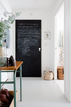 The chalkboard-painted bathroom door is an attractive and useful feature in the entryway.