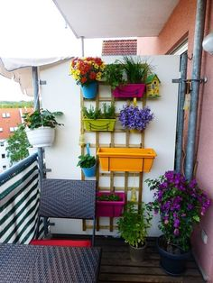 Vertical Balcony Garden Idea - Colorful planters are hung on this wooden bracket mounted on the wall.