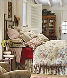 Great bedroom with plaid pillows, floral duvet, hat on headboard. Just so cozy.