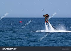 CAMYUVA, KEMER, TURKEY - JULY 12, 2015: Unidentified Turkish man hovered above the water with bent and straightens equipment. Extreme water sports are increasingly popular on the beaches of Turkey