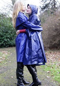 Two girls embracing in blue raincoats and black rubber boots