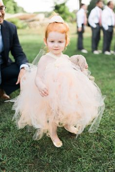 The sweetest flower girl in peachy tulle: http://www.stylemepretty.com/massachusetts-weddings/rockport-massachusetts-united-states/2015/11/20/high-school-sweethearts-labor-of-love-wedding-in-rockport-massachusetts/   Photography: Ruth Eileen - http://rutheileenphotography.com/