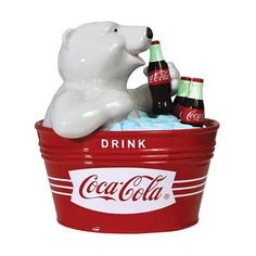 """From the Coca-Cola Collection, it's the Coca-Cola Polar Bear Cookie Jar! This ceramic cookie jar measures 9 3/4-inches tall, and features the polar bear from the Coca-Cola commercials sipping a Coke from inside a red ice bucket that reads, """"Drink Coca-Cola."""" The Polar Bear Cookie Jar makes the perfect gift for the vinDescriptione Coke collector! Item weight: 4.5 lbs. 9¾"""" tall. Ceramic. UPC: 748787"""