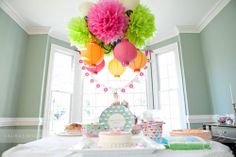 Claire's sweet first birthday party tissue pom and paper lantern cluster over dessert table