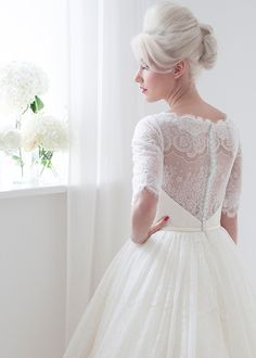 Primrose - Primrose is a beautiful sophisticated full lace gown shown in vanilla with ivory lace overlay. An elbow length sleeve for coverage but coupled with a low back bodice and sheer illusion panels for added elegance.