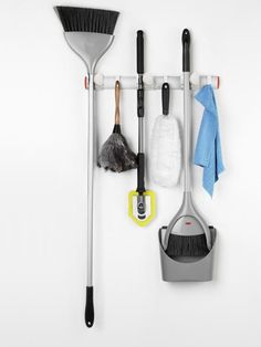 Organize cleaning supplies with an innovative wall-mounted storage unit. OXO's expandable wall-mounted organizer holds up to 12 long-handled items, including brooms, mops, duster, and umbrellas. The holders automatically adjust to grip specific poles, and you can remove them or customize spacing. Eight additional hooks add even more storage. Photo courtesy of OXO