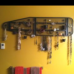 I created a wall art to hang all of my jewelry. It is made from an old ironing board, shower hooks, and small/medium metal craft buckets. I spray painted all the pieces separately and then put everything together.