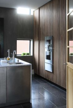modern minimal kitchen, black stone floors, slatted wood wall, grey concrete walls, built-in double oven, marble waterfall island