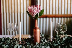 This wedding at the Cowshed was bohemian chic with blue, cranberry, and rose gold accents, a DIY macrame ceremony backdrop, and protea flower arrangements.