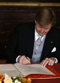 Prince Willem-Alexander of the Netherlands signs the Act of Abdication during the abdication ceremony of Queen Beatrix of the Netherlands in the Moseszaal at the Royal Palace on 30 April 2013