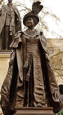 Bronze Statue of Queen Elizabeth (the Queen Mother) on The Mall, London, overlooked by the statue of her husband King George VI