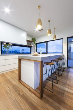 Denman Prospect Residence - Studio Black Interiors. A modern kitchen with a engineered stone concrete bench, timber features, white joinery, black fixtures, marble look subway tiles and brass pendant lights.