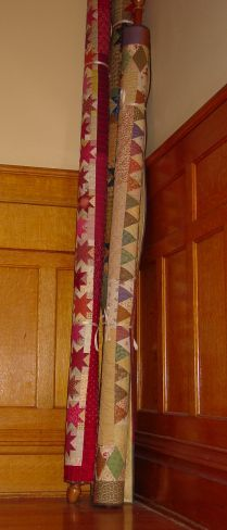 Quilts rolled on wooden closet rods with finials on the ends; tied with ribbons. These are leaning in the corner of the stair landing. Quilting With Judy Martin -- Lessons, Blocks, and Quilting Products From The World-Reknowned Quilter