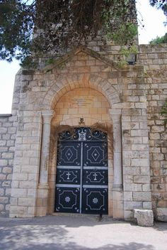 "Mt Tabor - St. Elias entrance -The symbol on the gate and above the door is ""TΦ"" (Tau + Phi)  meaning 'taphos' or 'Sepulchre' - the Holy Sepulcher. This is the symbol of the Greek Orthodox church.  The date below the symbol shows the year of the construction - 1911."