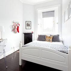 Cama encostada na parede  e com a cabeceira embaixo da janela para liberar mais espaço no ambiente.