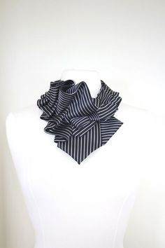 Two silk neckties are hand ruffled, formed, and stitched into our Aster shape. Our Ruffs are also lined with hand applied luxurious ribbon for added comfort Our sewn in dress snap is easy to find, we