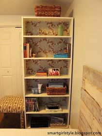 Pop the back off a cheap bookshelf and cover it with wallpaper or fabric