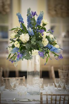 A tall slim square vase topped with a blue and ivory arrangement in the Orangery at Blenheim Palace