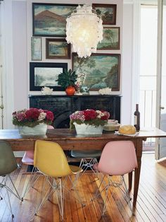 rustic with vintage details.  multicolored eames shell chairs, a collection of antique paintings, a capiz shell chandelier, and an antique fireplace.