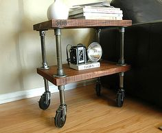Thick wooden shelves, aged iron piping and stenciled numbers give this next item true character. Once again, casters allow for motion, which can be handy for a side table in a small space. [from Vintage Industrial]