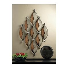 ELLIPSE WALL ART DECOR Make any wall a feature wall with the dramatic design and stunning style of this iron accent. Varying textures of metal blend to create an artistic wall piece that gives your room a designers flair. Materials: IRON