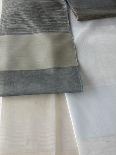 Modern csíkos organza függöny, csíkozás keresztben fut az anyagon, alul ólomzsinóros. Színek: tört fehér/drapp csíkos, szürke/drapp csíkos
