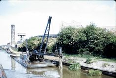 "Caption: ""GU Paddington Arm"" BW197/2/26/43  Image showing piling work being carried out near Southall in the 1960's, and the towpath bridge over wharf entrance to J. Lyons. #London #canal #Boat"