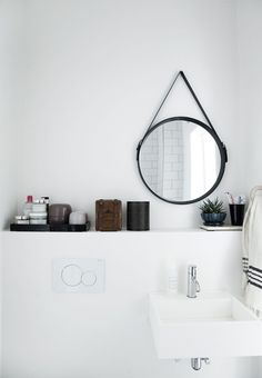Clean and nordic bathroom with a round mirror from Gubi and decorative storage for make-up and creams.