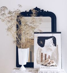 mantel with black vintage mirror with dried florals in white vase and modern graphic art print. / sfgirlbybay